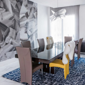 etoile suspension above a glass dining table inside Couture Modern Residence