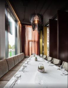 Aria black above a long dining table in the Brasserie Kennedy Restaurant